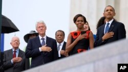 From left, former President Jimmy Carter, former President Bill Clinton, former U.N. Ambassador Andrew Young, first lady Michelle Obama, and President Barack Obama stand for the national anthem during the 50th anniversary ceremony.