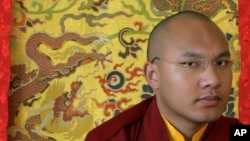 "Karmapa Lama, the third highest ranking Lama, pauses during an interview with Reuters in the northern Indian hill town of Dharamsala March 2, 2009. He is a ""living Buddha"" with an iPod, the 23-year-old possible successor to the Dalai Lama who may bridge t"