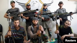 Free Syrian Army fighters pose for a photograph with their weapons in the old city of Aleppo, Sept. 16, 2013.