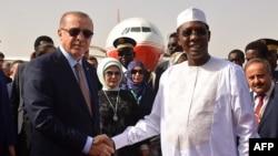 Le président turc Recep Tayyip Erdogan, à gauche, serre la main du président tchadien Idriss Deby, à son arrivée à N'Djamena, Tchad, 26 décembre 2017. AFP PHOTO / Brahim ADJI