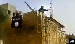 FILE - This June 2014 image taken from video shows Islamic State militants arriving at an oil refinery in Beiji, Iraq.