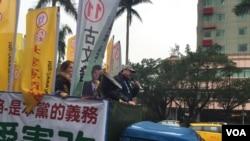 吾尔开希在竞选卡车上。他周四,即台湾选举日前夕,冒雨在台北街头做竞选宣传。(美国之音萧洵摄影)