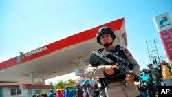 Seorang polisi siaga mengamankan sebuah SPBU Pertamina pasca bencana di Palu, Sulawesi Tengah (2/10).