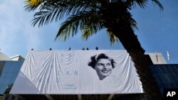 Workers place a banner depicting actress Ingrid Bergman on the Palais during preparations for the 68th international film festival, Cannes, southern France, May 11, 2015.