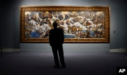 "FILE - A man looks at ""The Coronation of the Virgin, The Paradise"" a painting by 16th century Venetian artist Tintoretto at the Thyssen-Bornemisza Museum in Madrid, June 7, 2006."