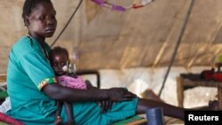 A woman carries her severely malnourished child at a clinic in Doro refugee camp in South Sudan, March 9, 2012.