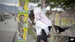 Man carries woman with cholera symptoms past campaign posters in Port-au-Prince (file photo)