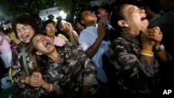 Warga Thailand menangis setelah pengumuman meninggalnya Raja Thailand Bhumibol Adulyadej di luar rumah sakit Siriraj di Bangkok, Thailand, Kamis (13/10).