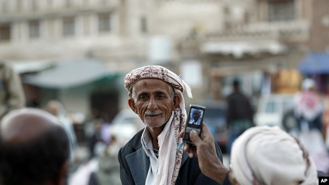 A Yemeni man, right, uses his mobile phone to take photos of his friend as they gather near the historical site of Bab al-Yemen in the the old city of Sana'a, Yemen, Nov. 14, 2012.