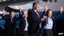 美国总统川普(右二)和曾被朝鲜关押的三名韩裔美国人走下刚刚抵美的飞机,走在马里兰州安德鲁斯联合基地的停机坪上。(2018年5月10日)