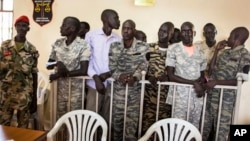 FILE - South Sudanese soldiers listen to the guilty verdict being delivered Sept. 6, 2018, at their trial for rape and murder in a violent rampage in 2016 at a Juba hotel.