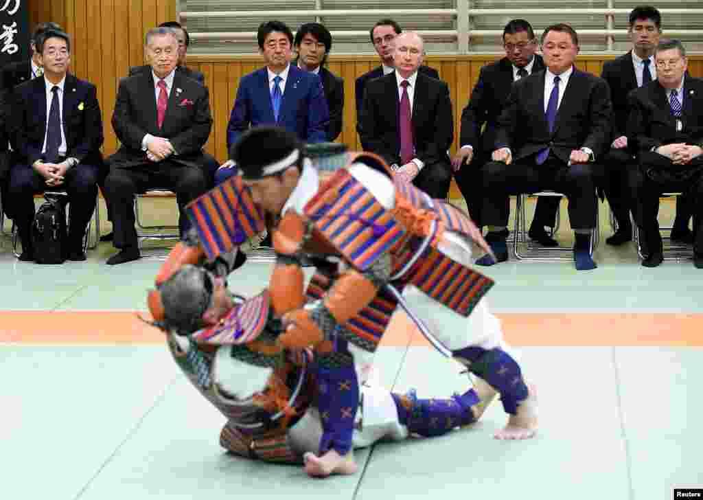 ولادیمیر پوتین، رئیس جمهوری روسیه، همراه با شینزو آبه نخست وزیر ژاپن، و یوشیرو موری نخست وزیر سابق ژاپن، یک مسابقه در مرکز جهانی جودو در توکیو ژاپن را تماشا میکنند.