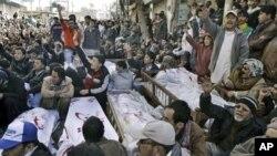 Người Hồi giáo Shia ngồi bên cạnh quan tài người thân trong cuộc biểu tình phản đối tại Quetta, ngày 12/1/2013.
