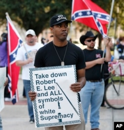 FILE – A man holds a sign during a rally led by the Take 'em Down Coalition, as confederate heritage supporters bear confederate flags nearby in front of City Hall in New Orleans, Dec. 10, 2015. Backlash has stalled work to remove Confederate monuments in New Orleans.