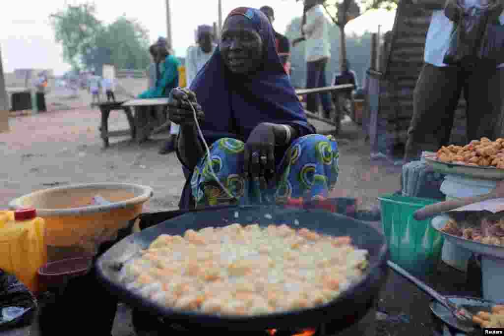 Nijerya'da iftar yemeği için sokakta yemek pişiren kadın. Kano, 21 Temmuz 2012