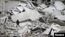 시리아 수도 다마스쿠스 인근 동부 구타의 미스라바 마을에 공습이 가해진 후 한 소년이 폐허가 된 건물 잔해 위를 걸어가고 있다.