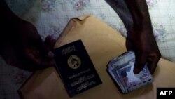 Un homme détient un passeport ghanéen et un rouleau de monnaie cedi ghanéen à Dormaa-Ahenkro, le 3 mai 2018.