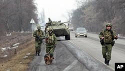 FILE - Interior Ministry officers patrol a road in the Russian North Caucasus on the hunt for Islamic State rebels, Jan. 28, 2011.