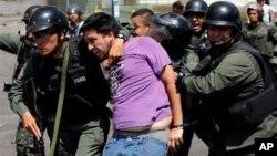 Miembros de la Guardia Nacional arrestan a un manifestante que se enfrentó a motociclistas armados partidarios del gobierno.