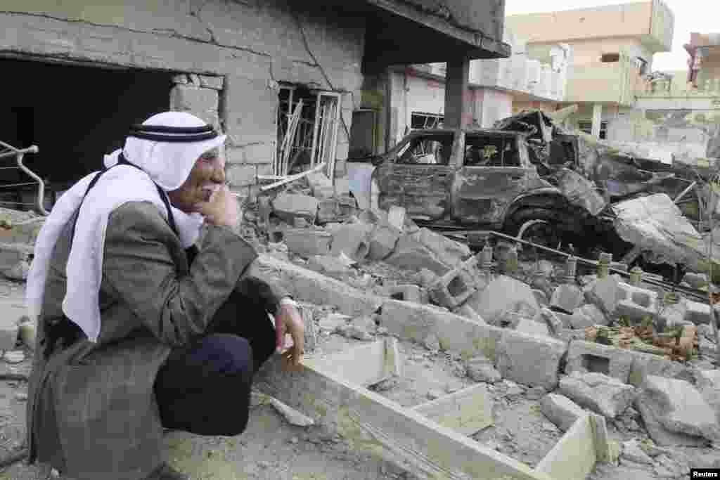 A man smokes a cigarette as he sits at the site of a bomb attack in Kirkuk, Iraq, March 29, 2013.