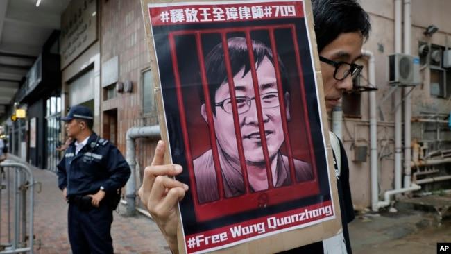 Một người biểu tình cầm một tấm hình của luật sư nhân quyền nổi tiếng Vương Toàng Chương đang bị cầm tù bên ngoài văn phòng liên lạc của Trung Quốc ở Hong Kong hôm 13/7/2018.