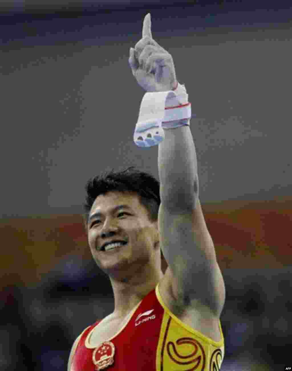 China's gymnast Chen Yibing, gestures after completing his routine on the men's rings at the 16th Asian Games in Guangzhou, China, Tuesday, Nov. 16, 2010. Chen won the gold medal. (AP Photo/Ng Han Guan)