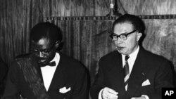 Patrice Lumumba, waziri mkuu wa Congo akitia saini tangazo la uhuru mjini Leopodville, Congo. Kulia kwake ni waziri mkuu wa zamani wa Ubelgiji Gaston Eyskens, aliyetia saini kwa niaba ya Ubelgiji. Ubelgiji iliitawala Congo kwa miaka 70.