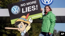 An activist with the environmental group Greenpeace protests Volkswagen emissions rigging. She stands outside a VW factory in Wolfsburg, Germany, Sept. 25, 2015.