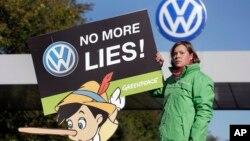 Seorang aktivis Greenpeace melakukan protes di depan pabrik Volkswagen di kota Wolfsburg, Jerman (25/9).