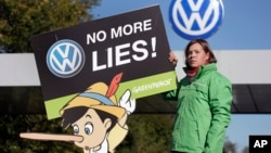 An activist with the environmental group Greenpeace protests Volkswagen emissions rigging. She stands outside a VW factory in Wolfsburg, Germany.