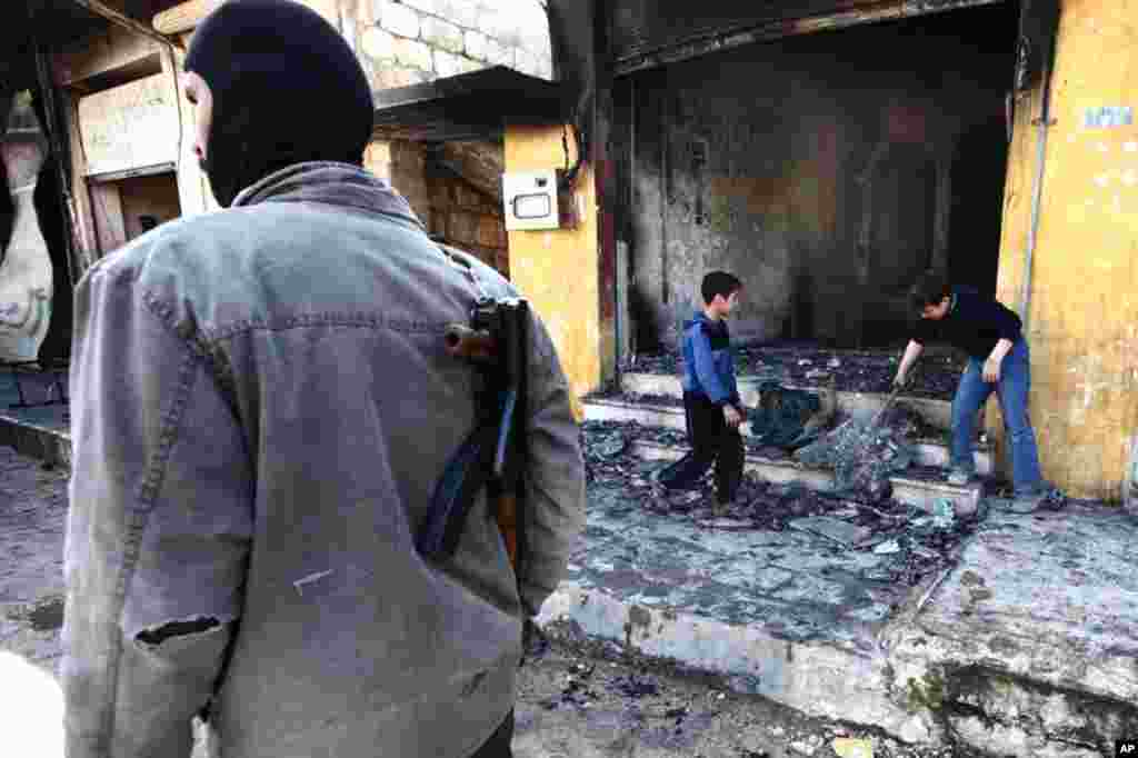 Children clean up a shop after heavy shelling by government forces near Idlib, February 28, 2012. (Reuters)