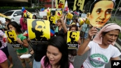 Protesters display placards showing national hero Apolinario Mabini, while shouting slogans outside the Chinese Consulate at the financial district of Makati city east of Manila, June 12, 2014.