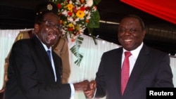 FILE - Zimbabwe President Robert Mugabe (left) with Prime Minister Morgan Tsvangirai, Harare, May 22, 2013.