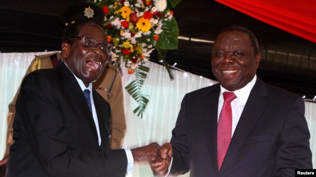Zimbabwe President Robert Mugabe jokes with Prime Minister Morgan Tsvangirai, Harare, May 22, 2013.