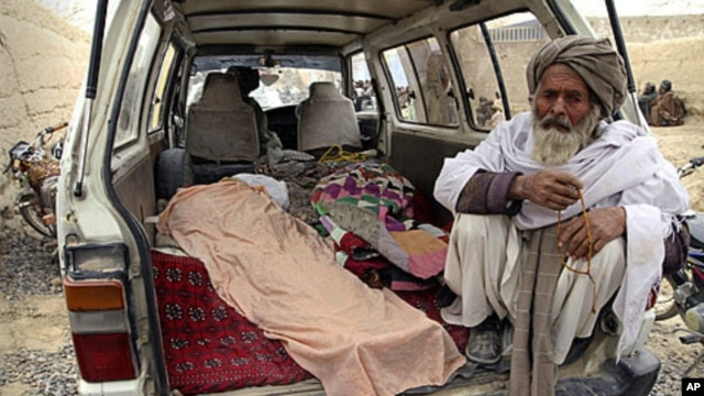 An elderly Afghan man sits in a minivan next to the covered body of a person allegedly shot dead by a U.S. service member in Panjwai, Kandahar province, Afghanistan, Sunday, March 11, 2012.