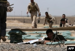 FILE - Iraqi Kurdish forces fight Islamic State militants in the Iraqi village of Bashir, June 29, 2014.