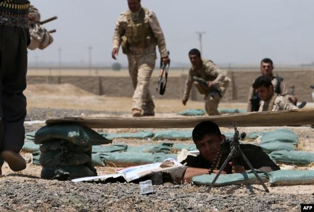 FILE - Iraqi Kurdish forces fight Islamic State militants in the Iraqi village of Bashir, June 29, 2014.