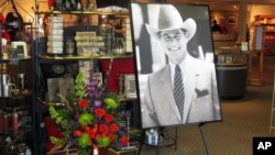 "A large portrait of Larry Hagman and a bouquet of flowers are placed at the entrance of the gift shop at Southfork Ranch, where Hagman played the infamous J.R. Ewing for the TV series ""Dallas,"" Parker, Texas, November 24, 2012."