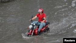 A motorcyclist drives on a flooded road after a heavy rainfall in Istanbul, Turkey July 18, 2017.
