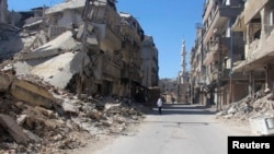 A resident walks past damaged buildings in the Damascus suburb of Zamalka, Syria, May 2, 2014.