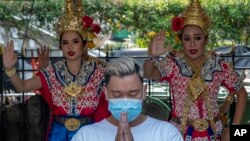 A man wearing a face mask pray at Erawan shrine as traditional dancers preform in Bangkok, Thailand, Wednesday, Jan. 29, 2020.