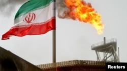 ایرانی پرچم کے پس منظر میں سروش آئل فیلڈ کے ایک پلیٹ فارم سے شعلہ بلند ہو رہا ہے۔ فائل فوٹو
