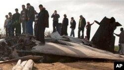 Libyans inspect the wreckage of a US F15 fighter jet after it crashed in an open field in the village of Bu Mariem, east of Benghazi, eastern Libya, March 22, 2011