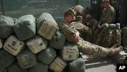 Tentara AS menunggu pemeriksaan barang-barang di luar kantor pabean Afghanistan di pangkalan Bagram, sebelum meninggalkan Afghanistan untuk kembali ke Amerika (14/7).