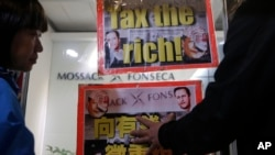 FILE - Placards featuring portraits of Chinese President Xi Jinping are displayed near an office of Panama law firm Mossack Fonseca in Hong Kong, April 12, 2016. The Panama Papers have shown relatives of members of the ruling elite owned offshore companies.