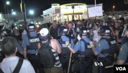 Police gather on street in Ferguson, Missouri, Aug. 10, 2015. (Photo: Kane Farabaugh / VOA)