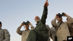 FILE - Photo by the government-controlled Syrian Central Military Media shows Iran's Army Chief of Staff Maj. Gen. Mohammad Bagheri, with binoculars, as he visits senior Iranian military officers in the northern province of Aleppo, Syria, Oct. 17, 2017.