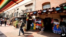 In this March 3, 2011 photo, tourists shop at Olvera Street stores at El Pueblo de Los Angeles Historic District in Los Angeles. (AP Photo/Damian Dovarganes)