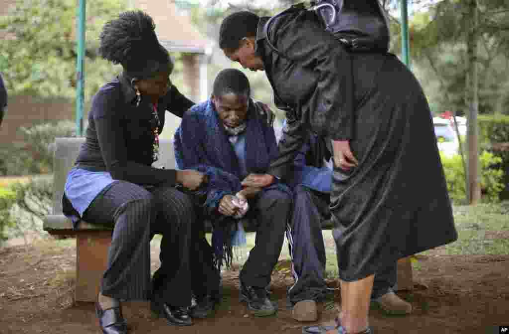 23일 케냐 나이로비 쇼핑몰 테러로 아버지를 잃은 남성이 부친의 시신 감안검시를 기다리는 동안, 친척들의 위로를 받고 있다.