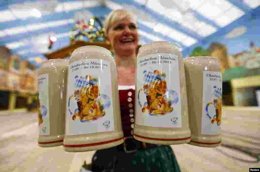 A waitress presents the official Oktoberfest beer mug during a presentation in Munich, Germany. The Oktoberfest, the world's biggest beer festival, runs from Sept. 21 until Oct. 6 this year.